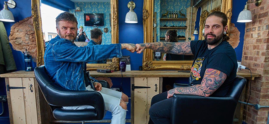 Matthew Pritchard and a barber sitting in barbers chairs, fistbumping