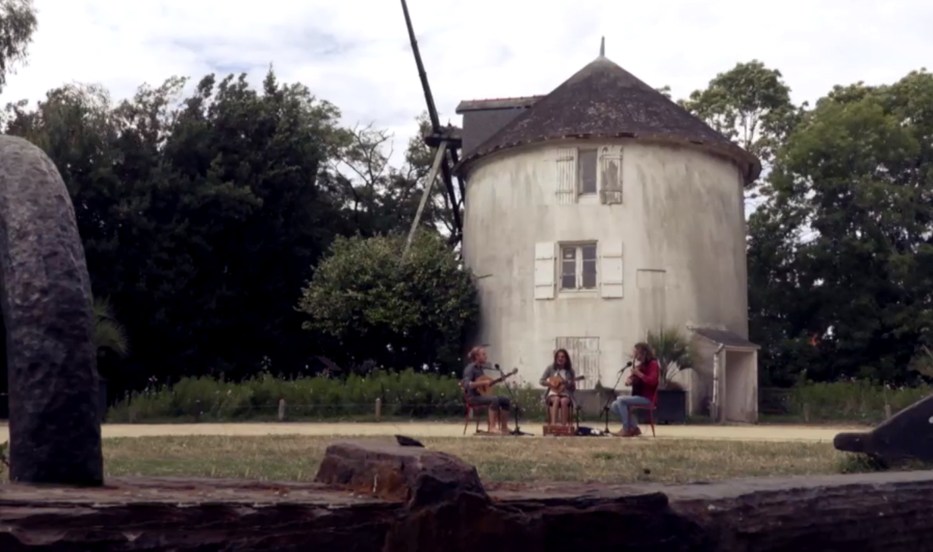 Three musicians playing in front of a windmill